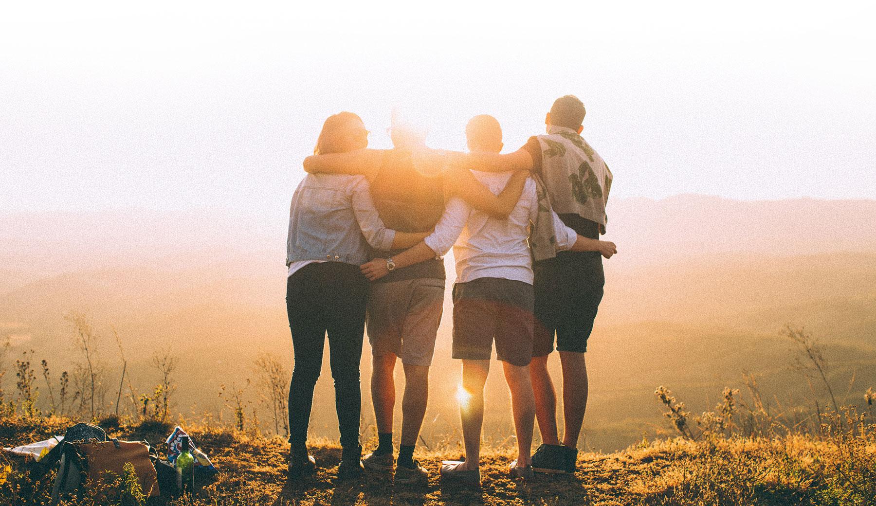 Junge Leute schauen in die Ferne und beobachten den Sonnenuntergang.